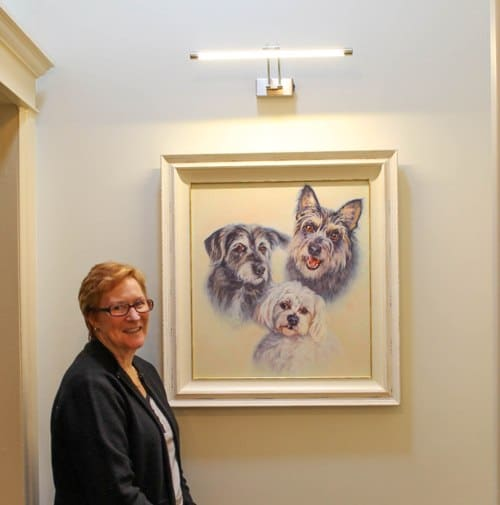 A photo of Chris with her portrait hanging