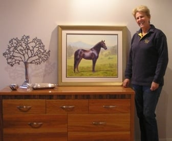 A lady with her portrait of a warmblood horse