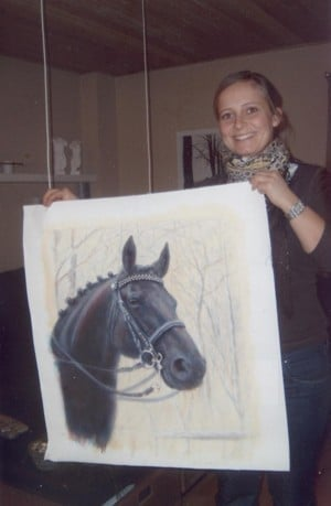 A girl holds the portrait of her horse