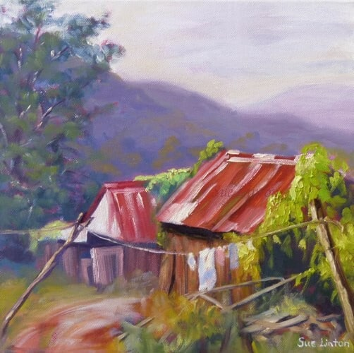 A landscape painting of some old sheds