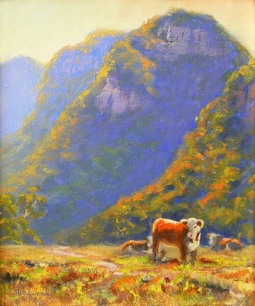 An australian landscape of cows below a craggy hill