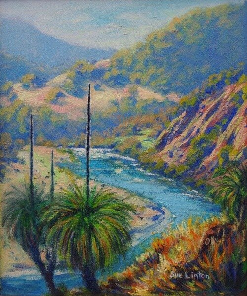 Australian landscape of a river with cliffs and grasstrees