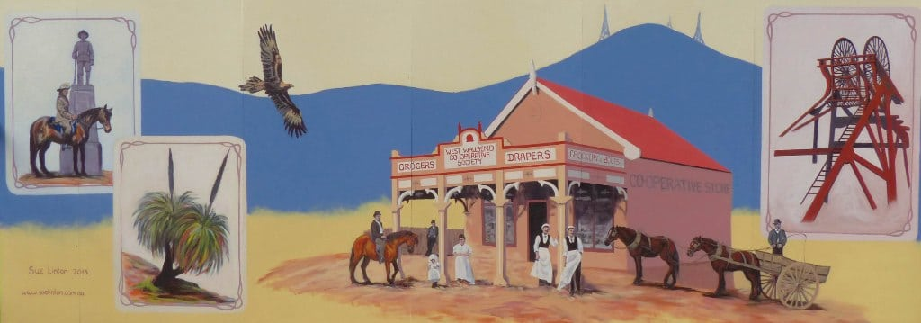 A mural with historic buildings , horses and carts , mine poppethead and symbols of aboriginal significance
