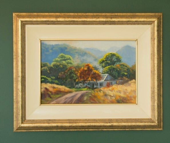 The painting is framed with a cream wooden slip with gold line and a mottled gold frame.