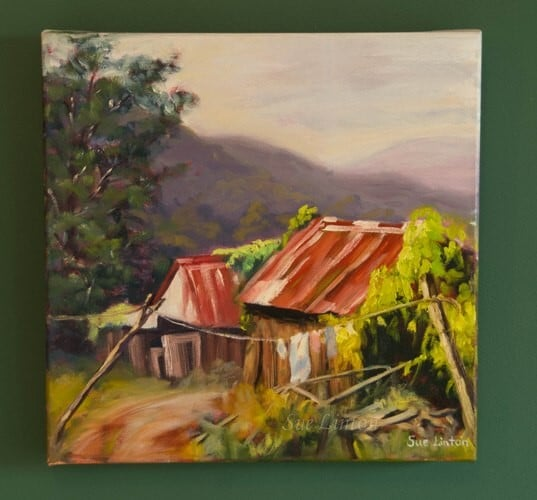 a painting of some old buildings and hills