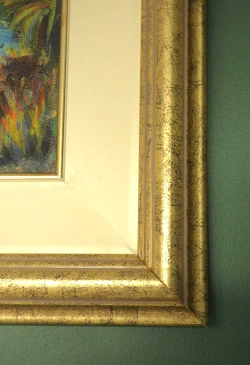 Frame detail - the frame is a mottled gold frame with an inner cream wooden slip with a gold line