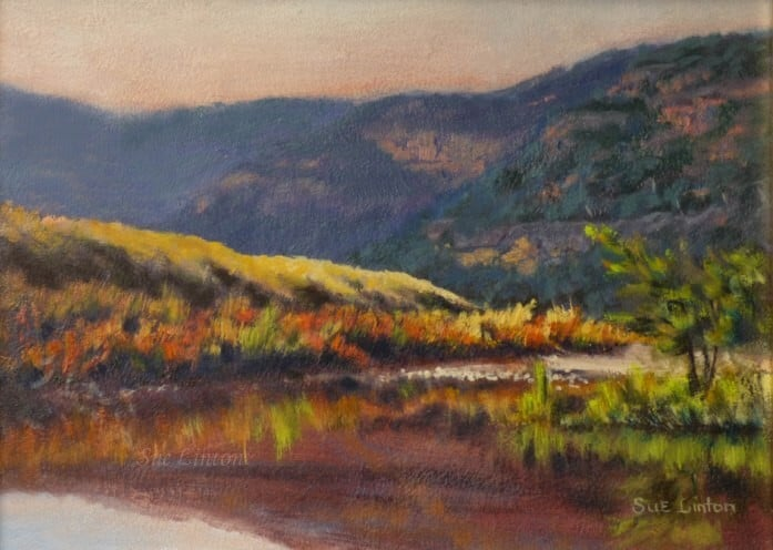 An Australian landscape of a river scene in the laet afternoon and rocky hills