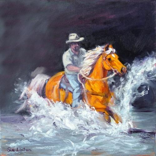 A stockman gallops his horse across a creek.