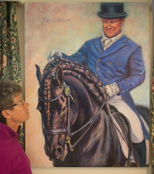 A portrait of a dressage rider on his Fresian Stallion
