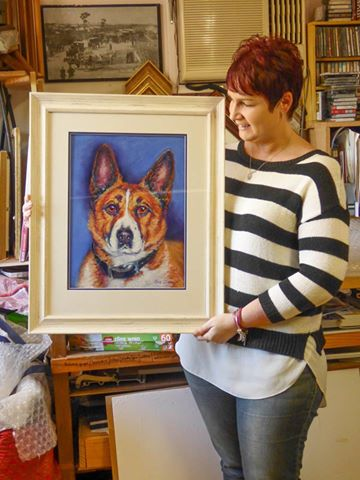 Tracey with her memorial dog portrait of Oscy created from photos