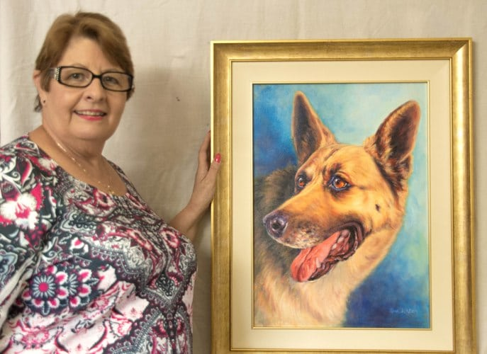 A happy Anne with her memorial dog portrait of her Alsatian painted from a photo