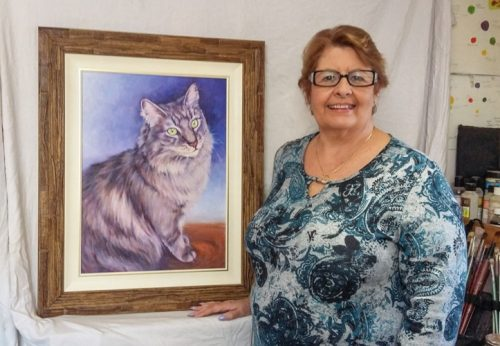 Anne with her memorial pet portrait of her cat